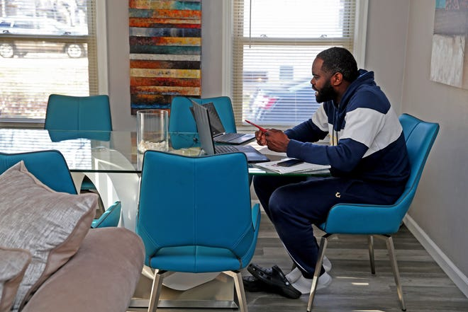 Jarvis Ragland, special education resource teacher at Marvin Pratt Elementary School, meets with students remotely in November at his mother's home. His mother, Shavodka Slaughter, was teaching her fourth grade class at Story Elementary School at the home at the same time.
