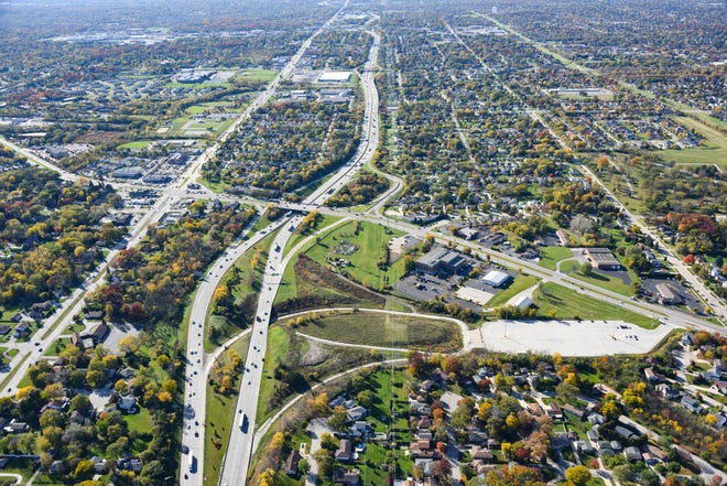 An aerial view shows the location of a proposed 38-acre development in the city of Greenfield. The view, which looks west, shows Interstate 894 running vertically in the frame, with Layton Avenue to its left. Loomis Road cuts across the image from upper-left to lower-right. The $100 million development would include a hotel, an entertainment/recreational business, gas station and a mix of residential, commercial, retail, office and medical space. The hotel would be located either north or south of the I-894/Loomis interchange. The entertainment space is eyed for a location near the park and ride parcel at lower-right.