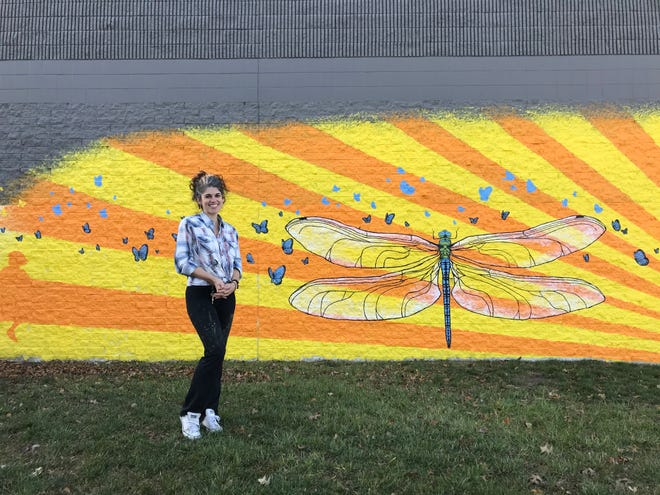 Lenise Alexandra Sunnenberg poses for a photo in front of a mural she painted outside Indian Mound Mall.
