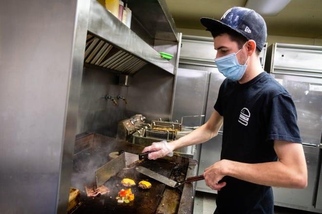 Zac Meldrum, owner of 7th Street Slider Bar, prepares food in the restaurant's kitchen Wednesday, Nov. 11, 2020. Meldrum opened the restaurant during the coronavirus pandemic.