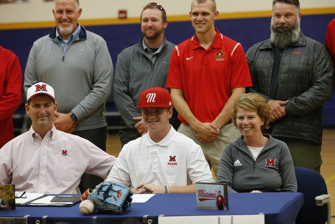 Seton Catholic pitcher Luke Leverton surrounded by family and coaches after signing with Miami University in Oxford, Ohio.