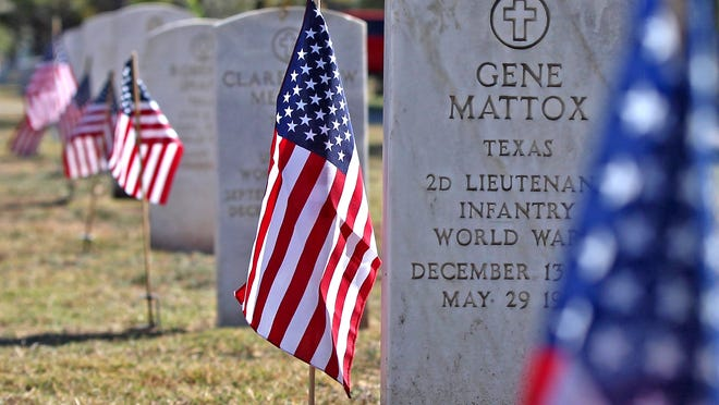 Grave sites of veterans are honored with American flags during a Veterans Day ceremony at Fairmount Cemetery on Wednesday, Nov. 11, 2020.
