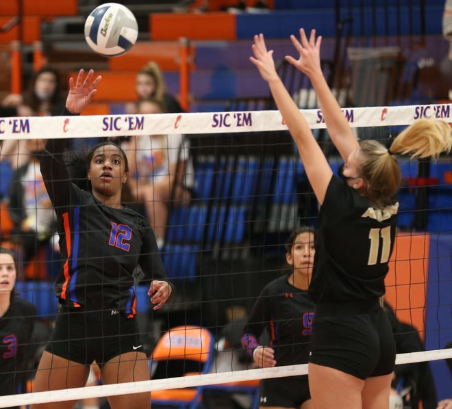 San Angelo Central High School's Kameryn Daniels, 12, goes up for a kill as Abilene High's Sarah Cox tries to block it at Babe Didrikson Gym on Tuesday, Nov. 10, 2020.