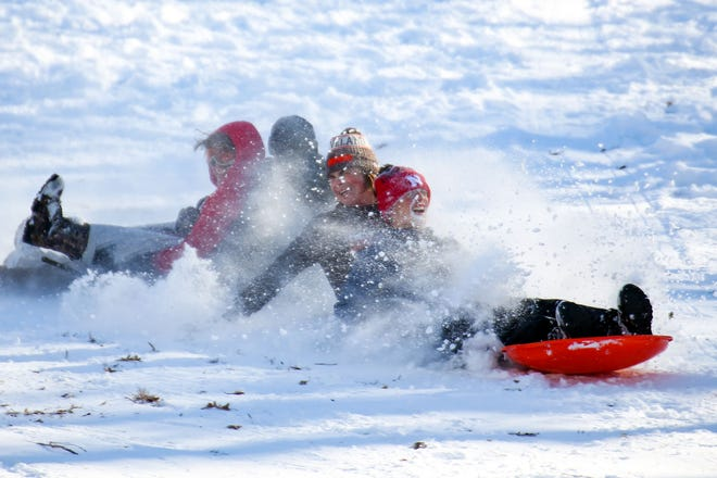 A group of sledders gets snow in their face as they try to make it down the hill while connecting four separate sleds on Wednesday, November 11, at Tuthill Park in Sioux Falls. This is the first lasting major snowfall of the season.