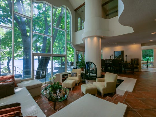 From the foyer, glimpses of the sunken living room with its built-in furniture and a three-story lakeview window come into view.