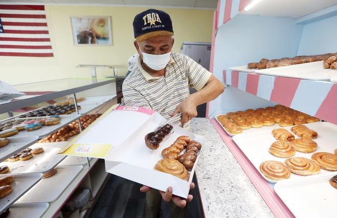 Kun Ouch readies a box of donuts at Happy Donuts on Maple Avenue in Zanesville. Ouchs and his wife Mayana Yim opened the shop in early November.