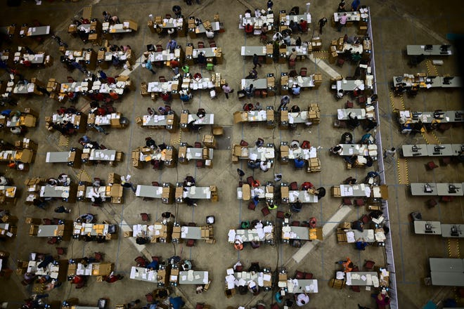 Officials count early votes at the Roberto Clemente Coliseum where social distancing is possible amid the COVID-19 pandemic, during general elections in San Juan, Puerto Rico, Tuesday, Nov. 3, 2020.