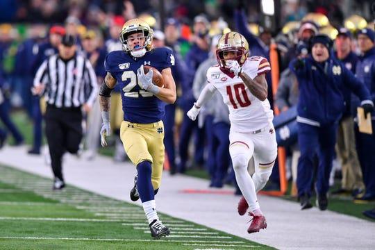 Notre Dame wide receiver Braden Lenzy (25) runs for a touchdown as Boston College cornerback Brandon Sebastian pursues during their 2019 game at Notre Dame Stadium.