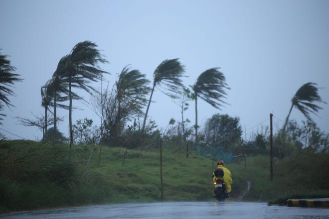 A motorist passes along a street amidst strong winds in Legazpi City in the Philippines Nov.11ahead of the landfall of Typhoon Vamco.