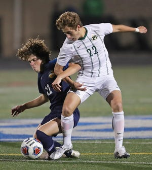 Medina's Braden Macauda, right, gets tangled up with St. Ignatius' Luciano Pechota as they battle for the ball during the first half of a Division I state semifinal soccer game, Wednesday, Nov. 11, 2020, in Brunswick, Ohio. [Jeff Lange/Beacon Journal]