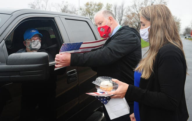 West Branch High School Principal Brian Coffee and assistant principal Evelyn Woods present veteran Jerry Mong with a flag poster made by one of the district's elementary students. Veterans were treated to a cinnamon roll and some gifts Wednesday during a drive-thru celebration on Veterans Day.