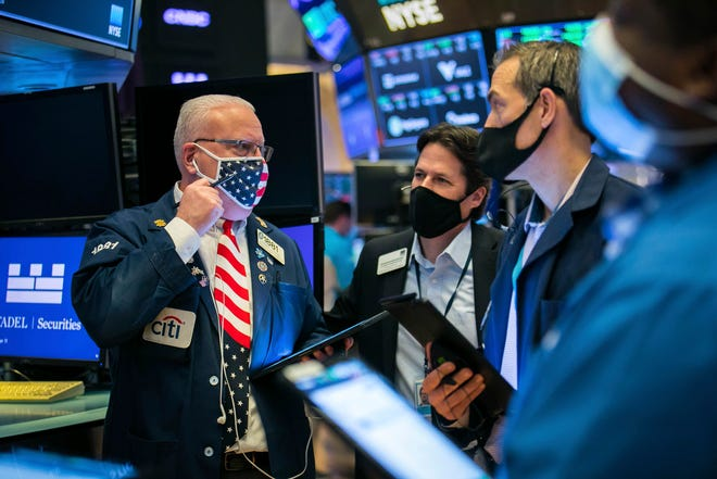 In this photo provided by the New York Stock Exchange, Thomas Ferrigno, left, works with fellow traders on the floor, Wednesday Nov. 11, 2020.
