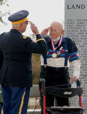 Retired Army Col. Tom Gray, commander of American Legion Post 196, and World War II veteran Gussie Seiler of Brownwood exchange salutes Wednesday during the Veterans Day observance at the Central Texas Veterans Memorial. Gray and post vice commander Harold Stieber presented Seiler with the World War II participation medal.