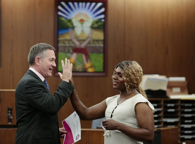Franklin County Municipal Court Judge Paul Herbert, left, congratulates Jewel Edwards after she graduated to level two during CATCH Court in June 2019. Herbert has announced that he will retire at the end of this year.