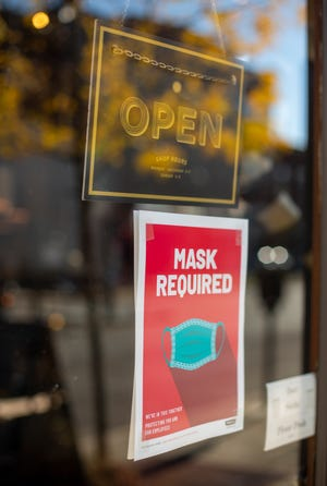 If it's essential that you venture out, wear a mask, as this business sign says, and social distance, says the president of IU Health East Central Region.