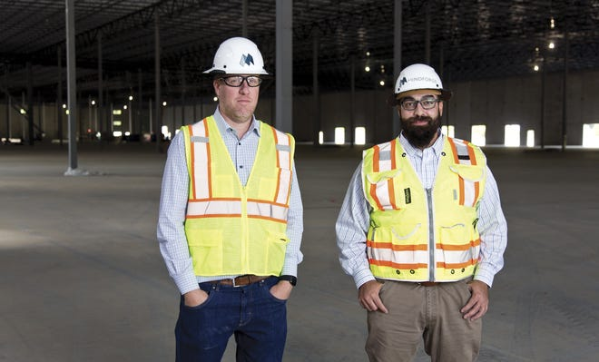 MindForge founder and CEO Stokes McIntyre, left, and vice president Shahin Aftabizedeh on a construction site