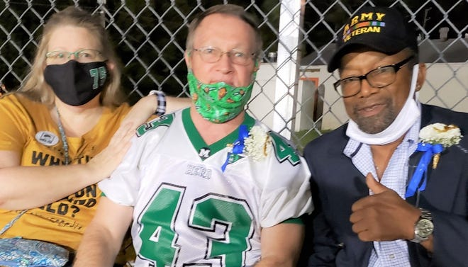 Carrie and Kevin Cottrell were accompanied by former Eustis Panther running back Melvin Benn, right, for the Eustis-Mount Dora football game on Nov. 6. Kevin called the coin toss before the contest, which commemorated the 50-year mark since his brother, Stuart Cottrell, perished in the Marshall University plane crash of 1970.