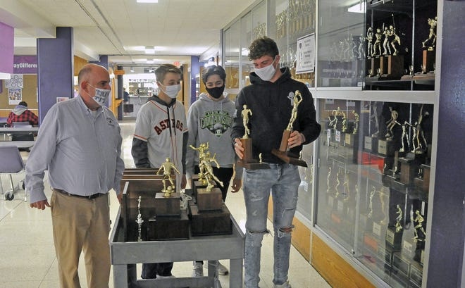 John Giltner, history and government teacher at Triway High School and chairman of the Triway Historical Committee, watches as Tyler Snyder, Gavin Stutz and Gaven Westfall photograph every trophy in the school's trophy cases Thursday. There will be no room for them in the new one-campus building, and photographs will be just one way the committee plans to preserve pieces of the past.