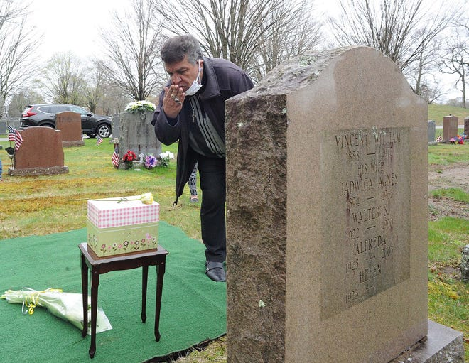 In this May 1, 2020, file photo, Jim Silvia blows a kiss during the burial of Helen Silvia, 97, of Brockton, at the Calvary Cemetery in Brockton. Helen Silvia died from the coronavirus at the Sachem Center for Health & Rehabilitation in East Bridgewater.