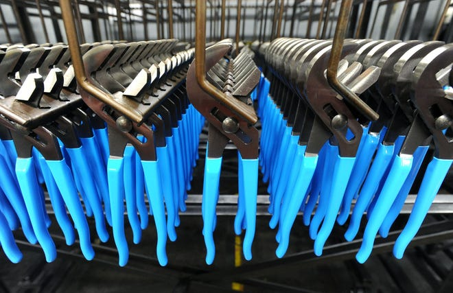 Nearly finished tools with recently dipped handles hang on a rack in this 2011 photo taken at Channellock Inc., in Meadville.