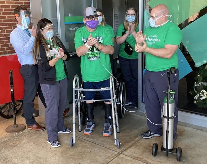 Chris Cleland, 65, walks out of Saint Vincent Hospital on Thursday after spending almost five months hospitalized with COVID-19. The Crawford County man is surrounded by the nurses and therapists who cared for him at Saint Vincent.