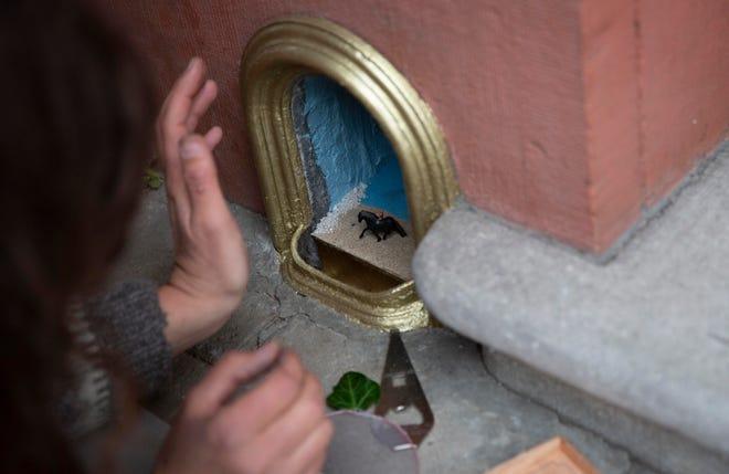 Artist Elke Lemmens installs a miniature scene of a girl on a horse into a boot scraper in Antwerp, Belgium.