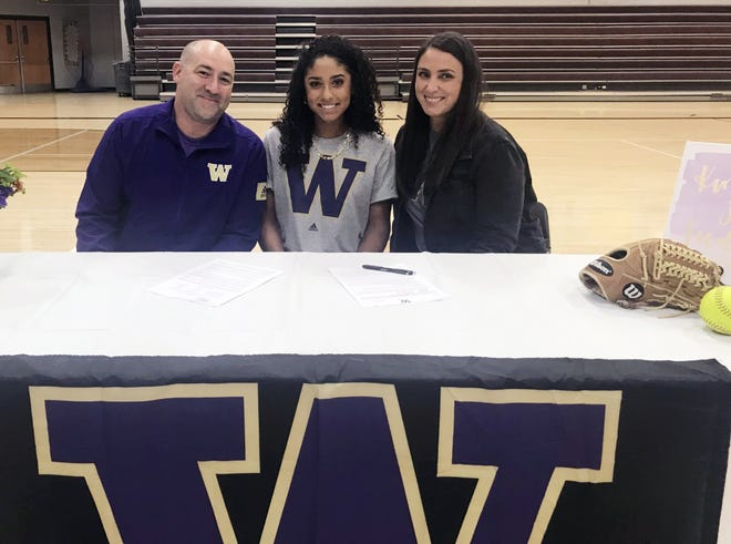 Lee's Summit North senior Kinsey Fiedler, one of the top softball recruits in the nation, poses with her parents Jason and Lacey after signing with the University of Washington Wednesday.