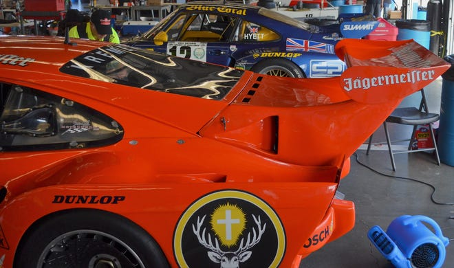 Two Porsche 935s garaged at Daytona International Speedway at the recent HSR vintage race there show off the race car's signature wide fenders and wild rear wing.