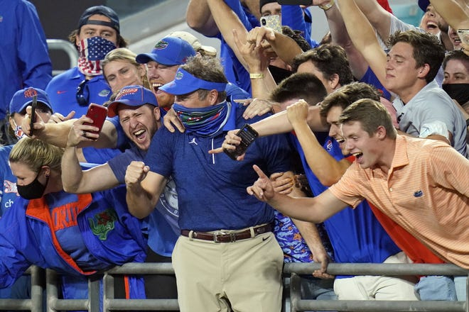 Southeastern Conference coaches like Florida's Dan Mullen, seen here celebrating with fans after the Gators beat Georgia 44-28 at TIAA Bank Field last week, can only hope having four games scratched on Saturday due to COVID-19 issues doesn't prevent them from completing a full season.