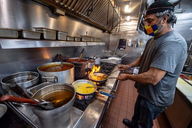 Guru's Fine Indian Cuisine in Newtown, owner/chef, Ashni Kumar Guru, preparing lobster bisque, and spicy coconut shrimp, Wednesday, Nov. 11, 2020.