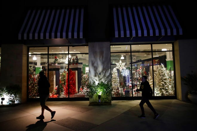Shoppers walk past a storefront with seasonal holiday products in Santa Clarita, California.