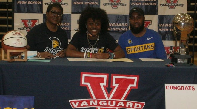 Vanguard's Nasia Powell, center, signs her National Letter-of-Intent to play basketball at the University of North Carolina at Greensboro as her parents, Steve and Annette, look on during Wednesday's ceremony.