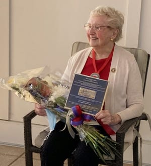 Betty Beecher, 96, of Weymouth holds a photo of the plaque honoring WWII's  U.S. Cadet Nurses which was placed this week in Nurses Hall at the  State House.