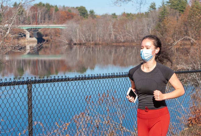 Madeleine Dawson jogs along the Riverwalk in Lewiston, Maine on Tuesday, Nov. 10, 2020. Dawson, a Bates College student, has been enjoying the warm weather the last few days and says that jogging while wearing a mask does not bother her at all. (Andree Kehn/Sun Journal via AP)