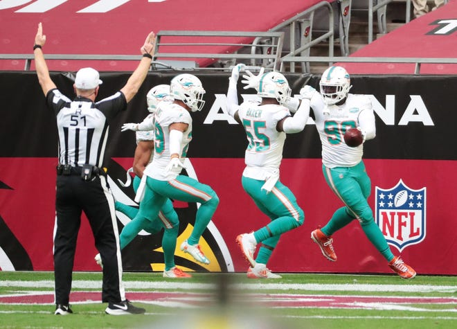 Dolphins defensive end Shaq Lawson (90) celebrates with his teammates in the end zone after recovering a fumble for a touchdown during last Sunday's win at Arizona.