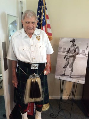 Stanley Johnston, of Jupiter, poses on his 90th birthday with a picture of himself as an infantry soldier during World War II. He will soon celebrate his 95th birthday.