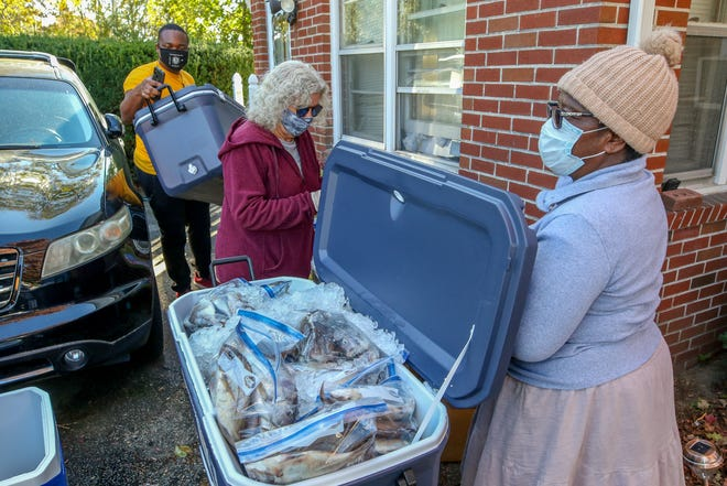 Working on distribution of fresh fresh in Providence, are, from rear to front is Theophilus D. Joseph, Jr. of Sunrise Forever, Inc., Susan Lepore of the African Alliance of RI and volunteer Martha Gweh from Sunrise Forever, Inc.