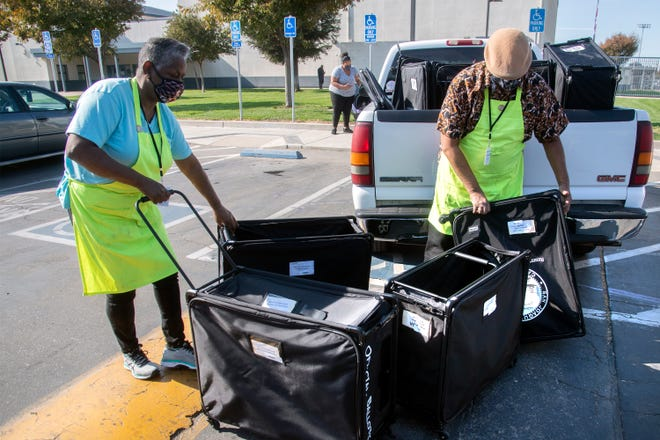 Election workers Mary Taylor, left, and James Brown ready new ballot boxes to be dropped off at the polling pace at Bear Creek High School in Stockton. Taylor and Brown were making rounds at polling places to pickup full boxes to be taken back to the Registrar of Voters office and dropping off new ones.  CLIFFORD OTO/THE STOCKTON RECORD