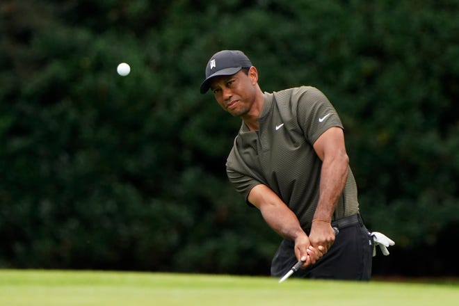 Defending champion Tiger Woods chips to the 15th green during Thursday's first round of the Masters.