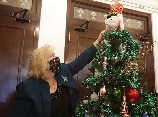 Susan Stuck, executive director of the Lincoln Theatre, puts the topper on a Nutcracker-themed tree that she decorated. It is one of 24 the theater is auctioning.