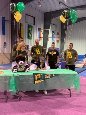 Perry High School senior Rakel Jeffries signs her letter of intent with Baylor as Diva Gymnastics Academy owner Lisa Ford (left) and the academy's coaches look on.