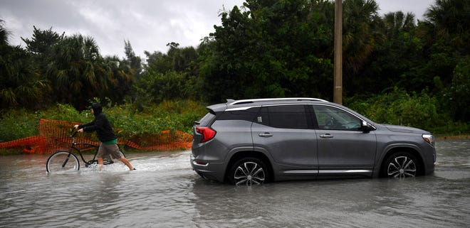 A cyclist pushes his bike through deep water and past a stalled car in Sarasota on Wednesday as Hurricane Eta was passing to the west.