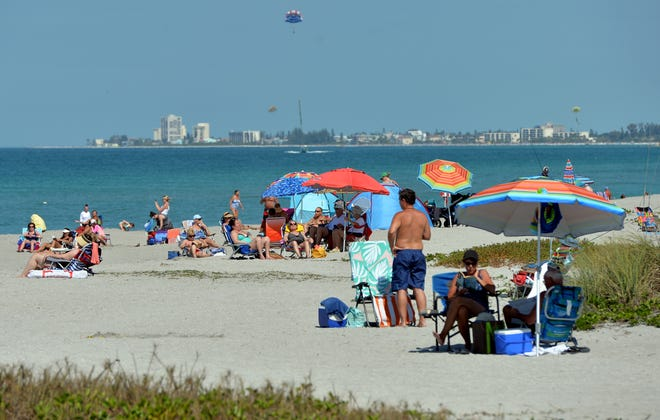 Beachgoers enjoy a morning at Turtle Beach in Sarasota, Florida on March 18, at the beginning of the coronavirus pandemic. COVID-19 is expected to have a significant impact on the upcoming winter tourism season.