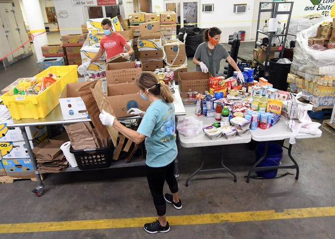 Volunteers sort out food from area grocery stores into boxes to be donated at the Food Bank of Central & Eastern North Carolina in Wilmington, N.C., Wednesday, April 22, 2020.