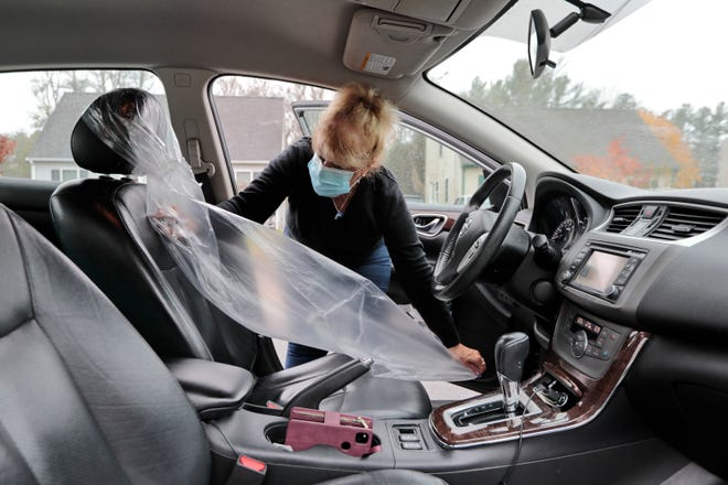 Upon arriving at the location she is picking up the student, Nacy M. Bernard of the Bernard's Driving Schoo on Union Street in New Bedford, wraps the driving seat in plastic for the students safety during the pandemic.