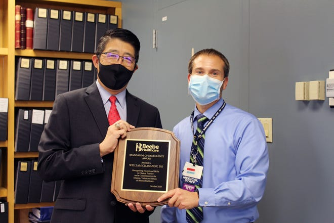 David A. Tam, president and CEO, Beebe Healthcare, awards Bill Chasanov with the 2020 Physician Standards of Excellence Award.