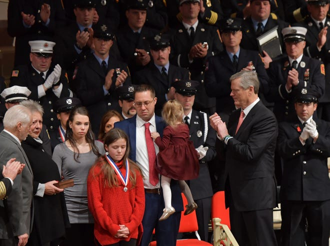 Ava Roy, in red, and her family accept a posthumous Medal of Honor for her father, Worcester Firefighter Christopher J. Roy, at the Firefighter of the Year Awards on Nov. 26, 2019, in Mechanics Hall in Worcester.