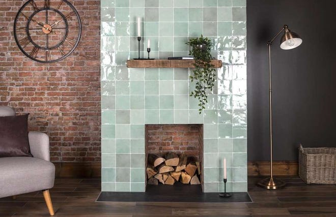 The simplicity and sparkle of the tile fireplace facing creates a striking contrast with the brick wall and firebox.