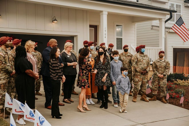 Alaina Money-Garman presents Legna Barreto, the Gold Star widow of Sgt. 1st Class Elis Angel Barreto Ortiz, with the keys to a new home in the Wendell Falls community on Nov.11.
