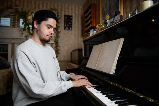 Michael Macias, a 21-year-old blind pianist who is a junior at Methodist University, plays the piano in his home.